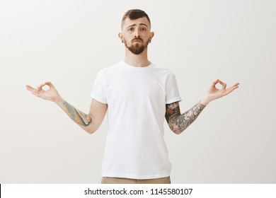 Portrait of calms and serious young guy looking like sensei, standing with spread hands in zed gesture and lifting curiously one eyebrow, meditating or practicing yoga over gray background - Shutterstock ID 1145580107