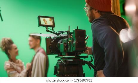 Portrait of Cameraman on Railway Trolley Shooting Green Screne Scene. Professional Crew on Big Budget Filmmaking. On Film Studio Set Shooting Historical Movie Green Screen Scene.