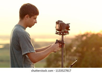 portrait of a cameraman shooting the sunset in the field, a young man making video with professional equipment walking on the nature in summer