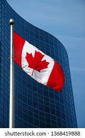 Portrait of Canadian Flag against a blue sky and building