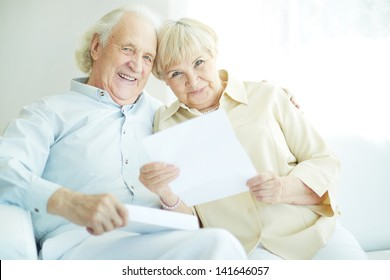 Portrait of a candid senior couple with paper looking at camera