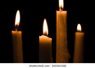 portrait of candles burning brightly on black background
