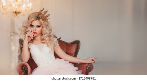 Portrait capricious princess girl. Blond hair gold crown. lady woman sitting in vintage armchair. backdrop white room lamp chandelier. Bored queen hand shows gesture on free space for text wide screen