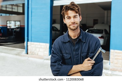 Portrait of a car mechanic in uniform with a spanner. Young mechanic standing with his arms crossed outside his workshop.