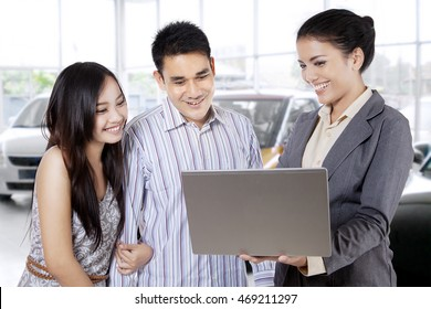 Portrait of car seller holding laptop and discussing with young couple about rule to buy a car in the showroom