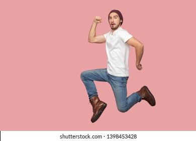 Portrait of carefree bearded hipster young man in white shirt and blue jeans with hat jumping in super mario pose and looking at camera with funny face. indoor studio shot, isolated on pink background