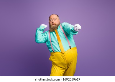 Portrait of carefree careless crazy bald man with big abdomen dance discotheque night club raise fists hands wear teal bright outfit isolated over vivid color background
