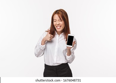 Portrait of carefree cheerful and satisfied smiling asian woman in shirt, skirt, showing mobile phone display with silly beaming grin, make thumb-up in like or approval, white background