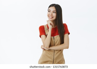 Portrait of carefree delighted and stylish female entrepreneur with long dark hair dreaming or thinking about perfect vacation looking left throught windown with cute nostalgic smile touching chin