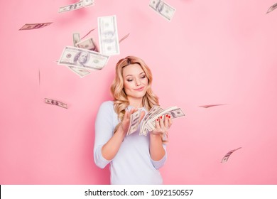 Portrait of carefree girlfriend, student wasting stack of much money, winner in casino lottery, having a lot of hundred dollars isolated on pink background