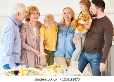 Portrait of carefree two generation family of six posing  at home and smiling happily while  standing at festive dinner table