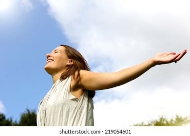 Portrait of a carefree woman smiling with arms spread open