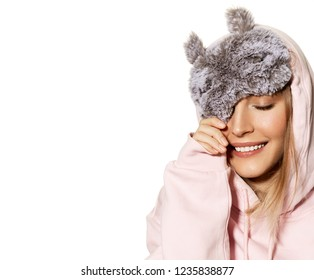 Portrait of carefree young blonde model smiling and wearing fluffy sleeping mask. Pretty girl with perfect clean skin posing in studio on white background