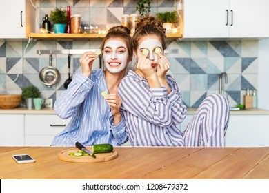 Portrait of carefree young models posing on kitchen in striped comfy pyjamas and having fun on nice interior. Youth skincare and friendship concept. Blurred background