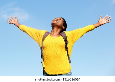Portrait of carefree young woman with arms outstretched outdoors
