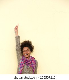 Portrait of a carefree young woman pointing finger up