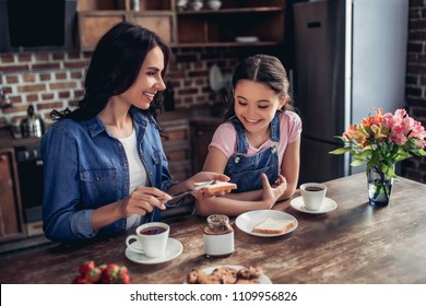 portrait of caring mother spreading toast with chocolate paste for her daughter in the kitchen