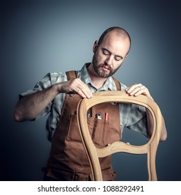 portrait of carpenter checking unfinished wood chair,studio shot