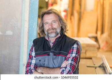 Portrait of a carpenter at the entrance of his workshop