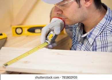 Portrait of a carpenter using a measuring tape