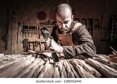 portrait of carpenter at work with hammer and gouge