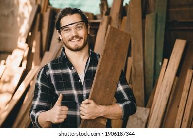 Portrait of Carpenter young SME furniture shop owner smiling in wood workshop look professional skilled real people handcraft workman.