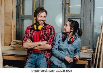Portrait of carpenters in the workshop. man and a girl, leaned back and posed, take a break from work. Startup, business concept. Jeans, checkered shirts. Ear protection, soundproof headphones.