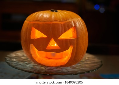 Portrait of a carved pumpkin for Halloween night with a candle inside to light up the scene.