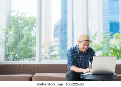 Portrait of casual asian businessman looking on laptop while sitting on sofa. Man and copy space for business, finance or insurance.