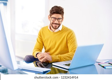 Portrait of casual businessman working on laptop while sitting at office and looking at camera.