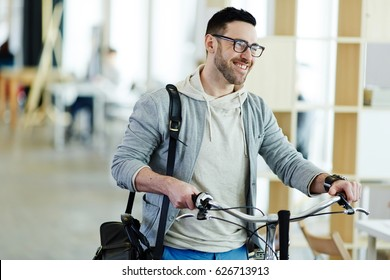 Portrait of casual contemporary business man taking bicycle to work in modern creative office