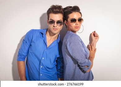 Portrait of a casual couple posing against a grey wall.