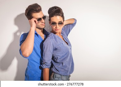 Portrait of a casual couple posing, she is holding her hand on her neck while he is fixing his glasses.