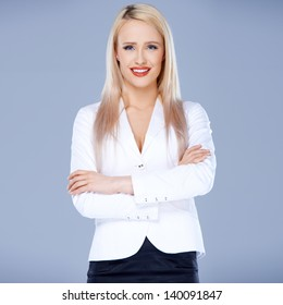 Portrait of casual dressed blond woman posing with arms crossed over natural background