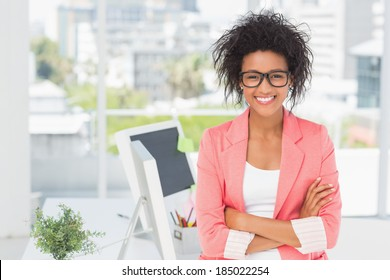 Portrait of a casual female artist standing with arms crossed at a bright office