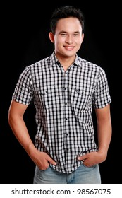 portrait of casual happy asian male smiling against black backgrounds