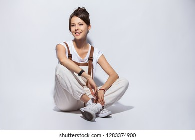 Portrait of a casual happy woman sitting on the floor on white background