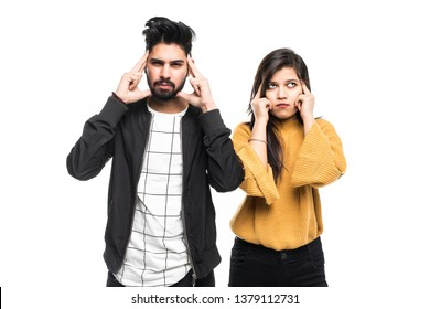 Portrait of a casual indian couple covering ears while standing and looking up isolated over gray background