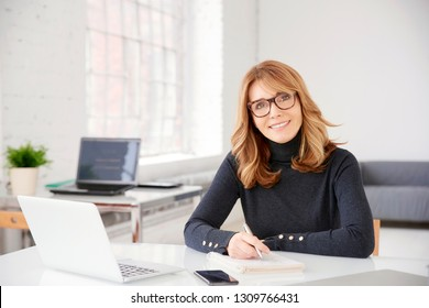 Portrait of casual mature businesswoman sitting at office desk while writing something and looking at camera.
