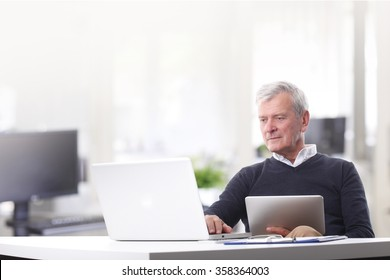 Portrait of casual professional man sitting at office in front of laptop and touching keyboard while holding in his other hand a digital tablet.
