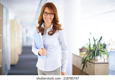 Portrait of casual sales woman holding file, while standing at office.