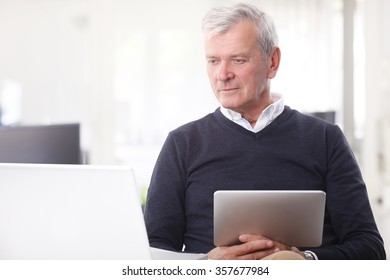Portrait of casual senior businessman sitting at office in front of laptop and holding in hand a digital tablet while working online.