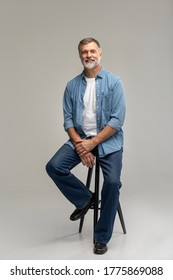 Portrait of a casual senior sitting on a chair on white background.
