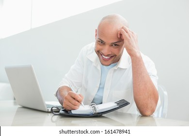 Portrait of a casual smiling young man with laptop writing in diary at home