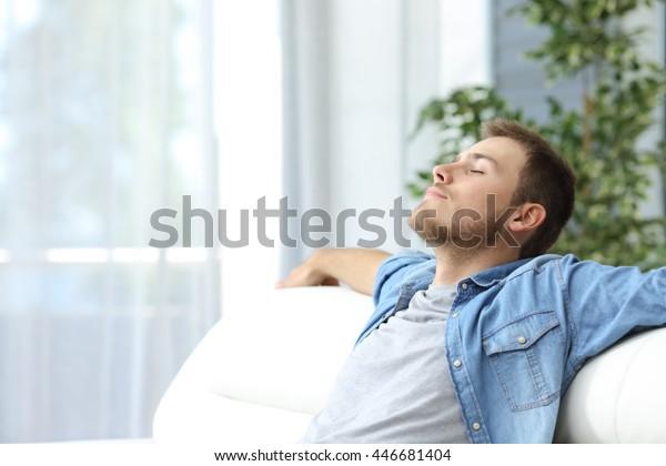 Porträt eines flüchtigen müden Mannes, der sich auf einer Couch zu Hause ruht