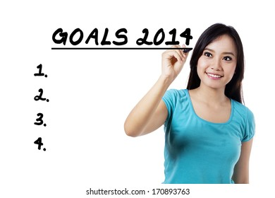 Portrait of casual woman writing the list of goals 2014