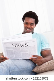 Portrait Of Casual Young African Man Reading Newspaper Sitting On Couch