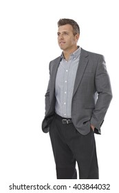 Portrait of casual young businessman standing hands in pockets, looking away.