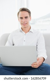 Portrait of a casual young man using laptop on sofa in a bright house