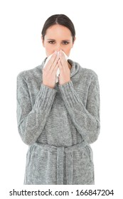 Portrait of a casual young woman suffering from cold over white background